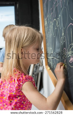 Portrait of little girl near the blackboard