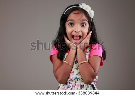 Portrait of little girl of Indian origin with a surprised face - stock photo