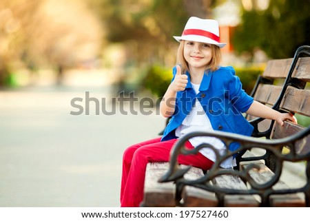 Portrait of little girl on bench in a park showing thumb up. Close-up. Happiness, fashionable concept. - stock photo