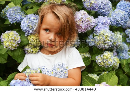 Portrait of little girl outdoor in a hydrangea garden smelling the flowers. - stock photo