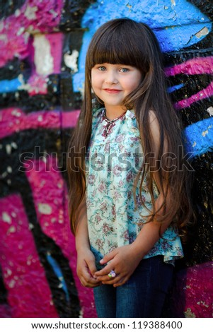 portrait of little girl outdoors in colored shirt