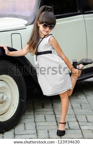 portrait of little girl outdoors in gray dress - stock photo