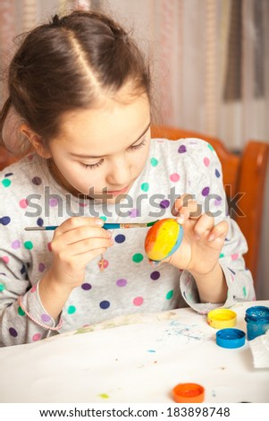 Portrait of little girl painting easter egg with watercolor - stock photo