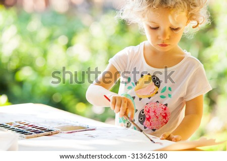 Portrait of little girl painting, summer outdoor - stock photo
