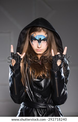 Portrait of little girl posing with the bat painted on her face