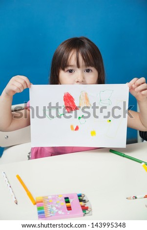 Portrait of little girl showing drawing paper in classroom - stock photo