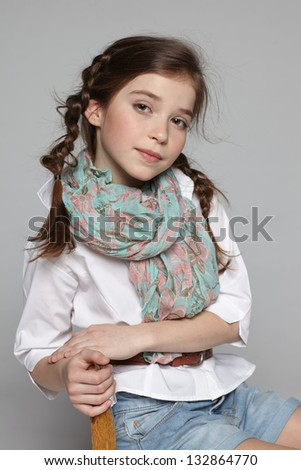 Portrait of little girl sitting on the chair - stock photo