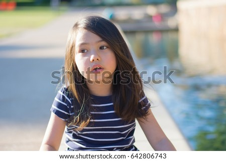 portrait of little girl smiling near by canal at park