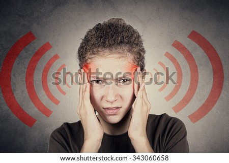 Portrait of  little girl suffering from headache and holding hands on her head.Stressed little girl having problems with red waving lines from head . - stock photo