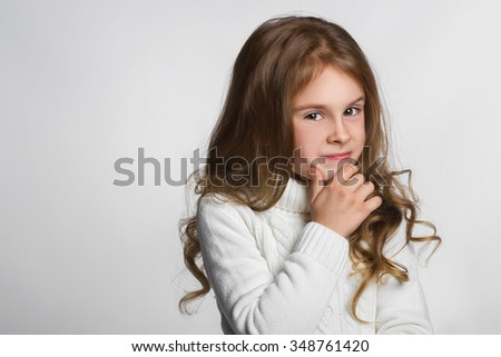 Portrait of little girl thinking, over a gray background - stock photo