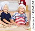 Portrait of little girl using cookie cutters on dough with sisters at kitchen counter - stock photo