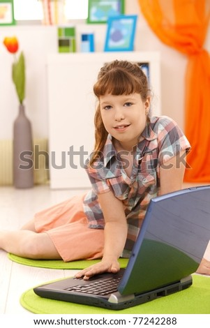 Portrait of little girl using laptop at home, looking at camera.? - stock photo