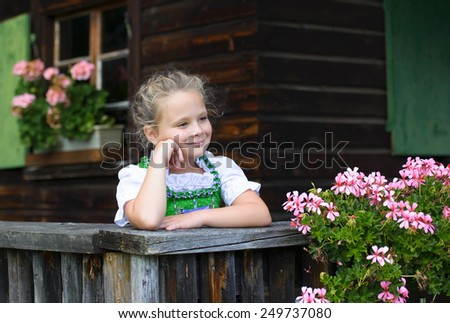 Portrait of little girl wearing a traditional Bavarian dress dirndl looking on outdoor house terrace  - stock photo