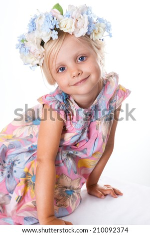 Portrait of little girl with a wreath of flowers.