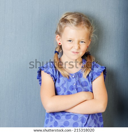 Portrait of little girl with arms crossed grimacing while standing against blue wall - stock photo