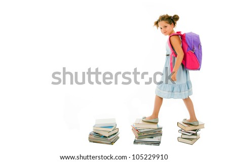 Portrait of little girl with backpack walking from top to top of book piles - stock photo