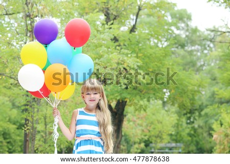 Portrait of  little girl with balloons in the park