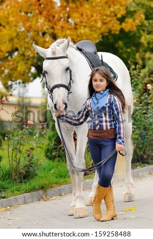 Portrait of little girl with big white horse in autumn