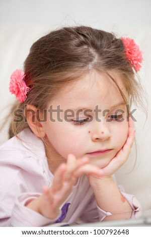 Portrait of little girl with chickenpox playing with tablet - stock photo