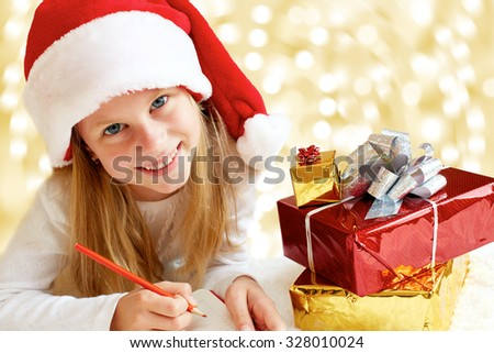 Portrait of little girl with Christmas gifts on the golden background. Christmas dreams. - stock photo
