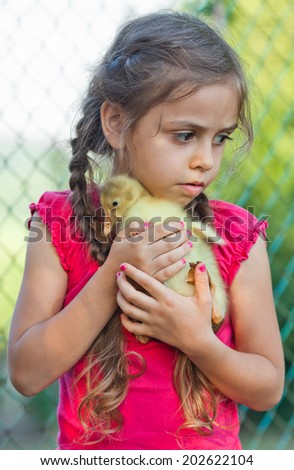 Portrait of little girl with goslings at the farm