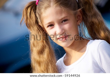 portrait of  little girl with long hair,smiling at the camera the blue
