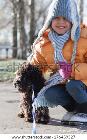 Portrait of little girl with miniature schnauzer in winter