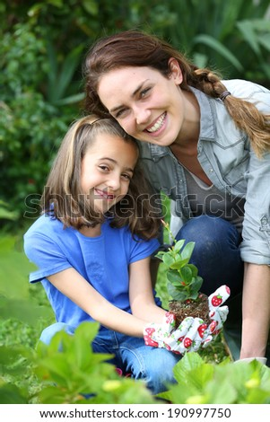 Portrait of little girl with mother in domestic garden - stock photo