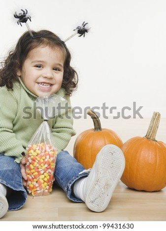 Portrait of little girl with pumpkins and candy corn