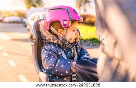 Portrait of little girl with security helmet on the head sitting in a bike seat behind of her father. Safe and child protection concept. - stock photo