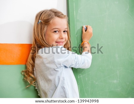 Portrait of little girl writing on green chalkboard in classroom - stock photo