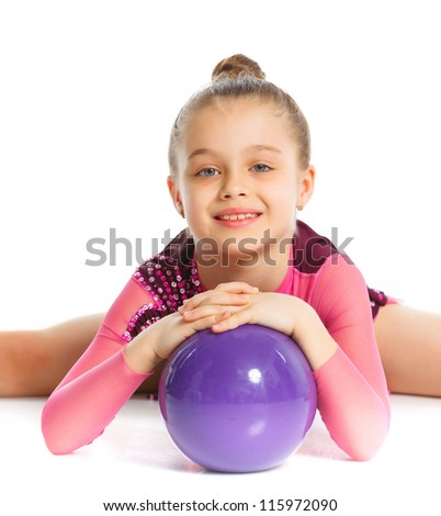 Portrait of little gymnast with ball on a white background. Sporting exercise, stretch, flexibility, aerobics