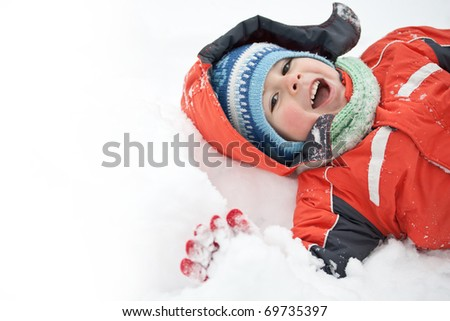 Portrait of little happy boy lies in snow
