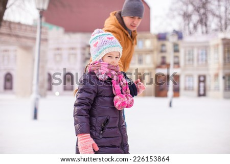 Portrait of little happy girl enjoying skating with her father - stock photo