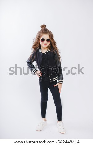 Portrait of little hipster girl in sunglasses. Posing. Curly modern hairstyle