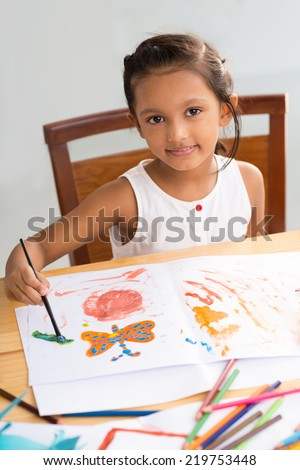 Portrait of little Indian girl painting butterfly