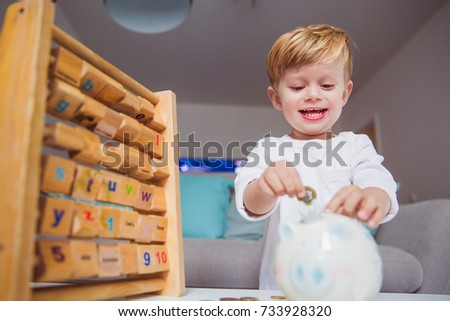Portrait of little joyful boy who throwing coins in piggy bank in the room