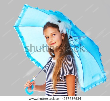 Portrait of little kid posing in studio with umbrella in rainy day