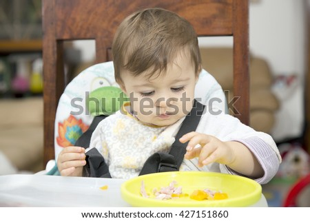 Portrait of little one year old baby at table eating food from a plate with hand