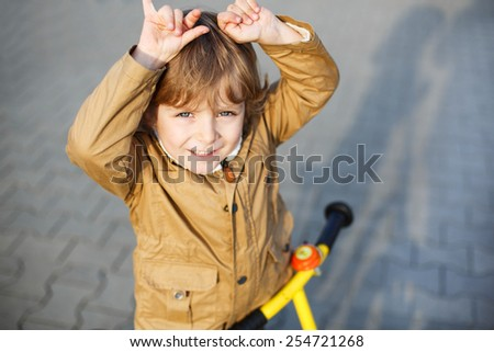 Portrait of little preschool boy having fun and riding his bike  in the city. Active leisure for kids, outdoor, on spring day. - stock photo