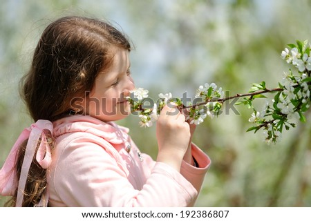 Portrait of Little pretty girl dreaming in the green garden