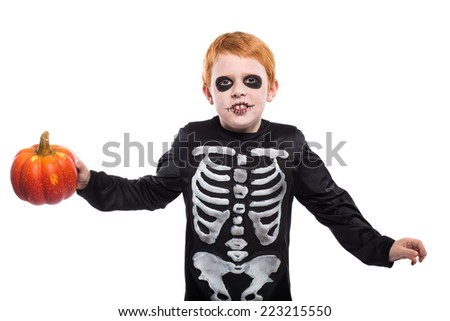 Portrait of little red haired boy wearing halloween skeleton costume and holding pumpkin. Studio portrait isolated over white background  - stock photo