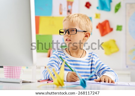 Portrait of little schoolboy in glasses sitting at the desk