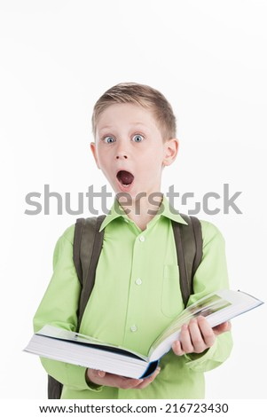 Portrait of little schoolboy with book on white background. boy opened book and expressing shocking emotions  - stock photo