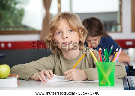 Portrait of little schoolboy writing in book at desk with classmate in background