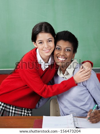 Portrait of little schoolgirl hugging female teacher at desk in classroom - stock photo
