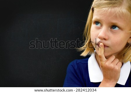 Portrait of little schoolgirl thinking standing at the blackboard. - stock photo