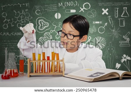 Portrait of little scientist doing experiment with chemical fluid in the laboratory - stock photo