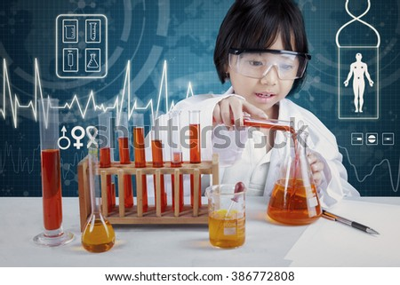 Portrait of little smart scientist doing research using chemical liquid in the laboratory - stock photo