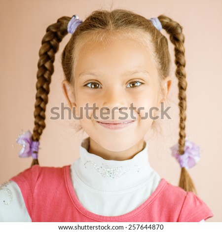 Portrait of little smiling beautiful girl on pink background. - stock photo